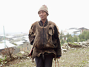 A Brokpa man wearing a sleeveless deer skin vest over his 'gho' a traditional long sleeved woollen tunic made from yak wool outside the Buddhist temple in Merak, Eastern Bhutan.