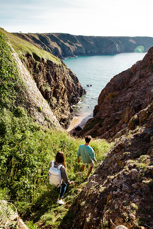 Couple exploring and walking down the cliff paths to a hidden cove at Plemont beach in Jersey, Channel Islands on a calm sunny Spring day