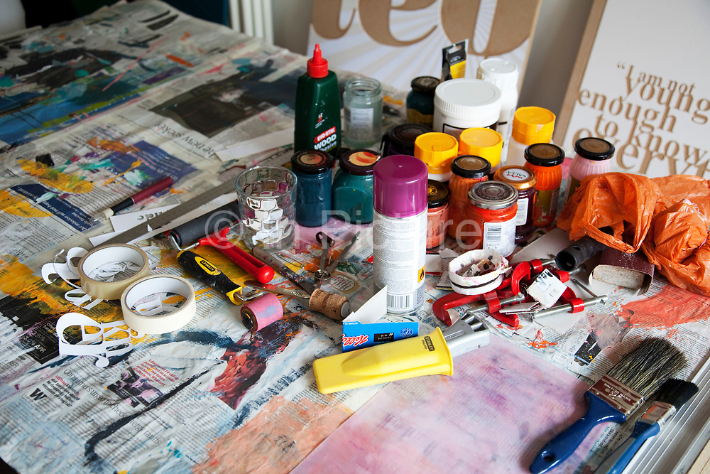 Still life of an artists work bench. Collection of paint and brushes and other various tools and mediums.