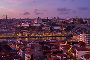 Historic river front of the Ribeira region of Porto at dusk and Dom Luis I bridge from Vila Nova de Gaia in Portugal