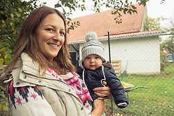 Portrait of a mother holding her baby son in her arms and smiling, Bavaria, Germany