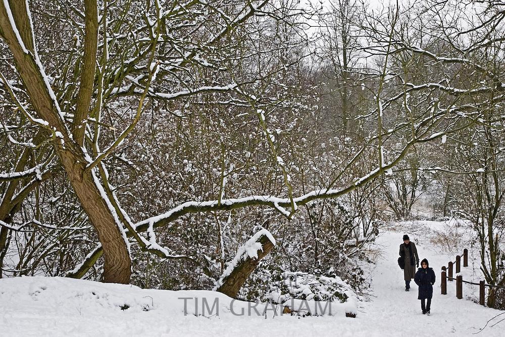 People walk across snow-covered Hampstead Heath, North London, United Kingdom