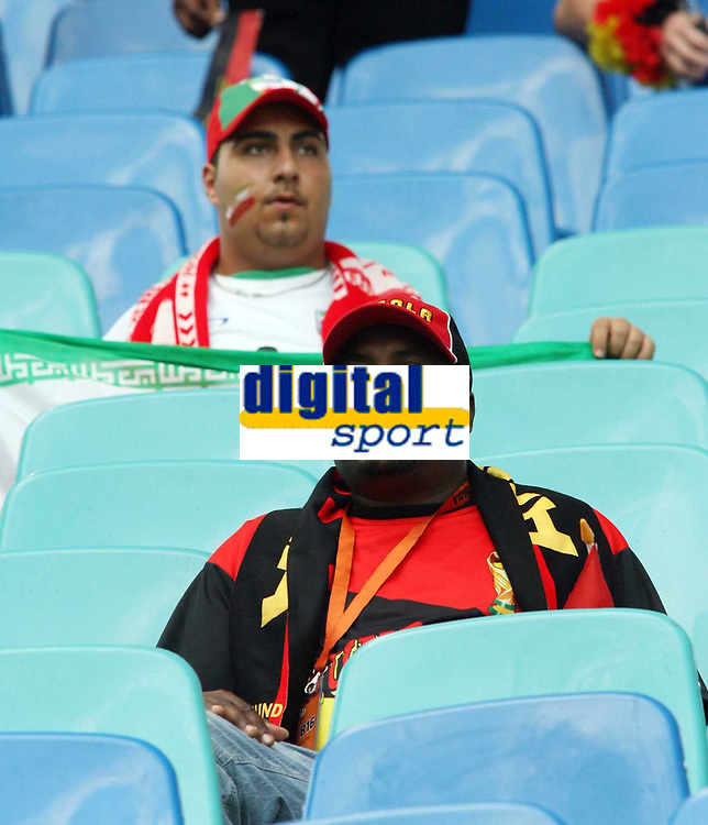 Photo: Chris Ratcliffe.<br /> <br /> Iran v Angola. FIFA World Cup 2006. 21/06/2006.<br /> <br /> An Iranian and an Angolan fan in a stadium with lots of empty seats.