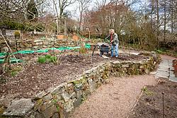 Carol adding fresh compost to the border in Annie's garden