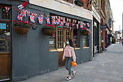 Chinese woman walks past the Golden Heart pub in Spitalfields wearing a face mask for protection as lockdown continues and people observe the stay at home message in the capital on 12th May 2020 in London, England, United Kingdom. Coronavirus or Covid-19 is a new respiratory illness that has not previously been seen in humans. While much or Europe has been placed into lockdown, the UK government has now announced a slight relaxation of the stringent rules as part of their long term strategy, and in particular social distancing.