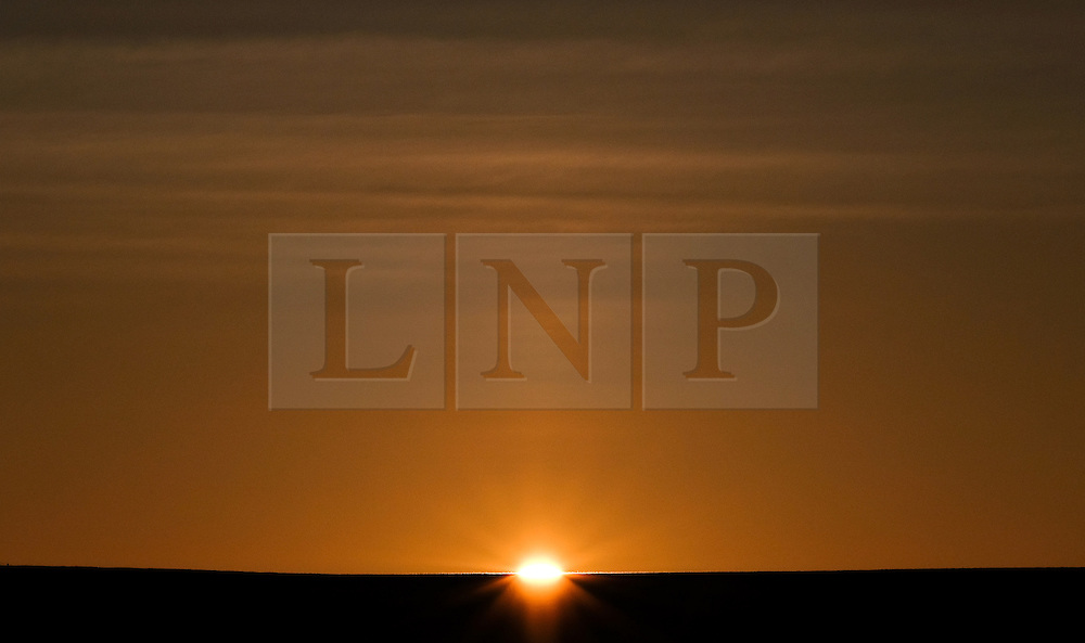© Licensed to London News Pictures.02/10/15<br /> Staithes, UK. <br /> <br /> The sun rises over cliffs overlooking the harbour in the North Yorkshire village of Staithes on the east coast as the warm autumn weather continues.<br /> <br /> Photo credit : Ian Forsyth/LNP