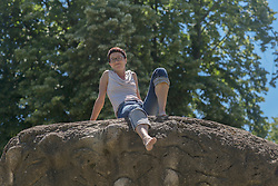 Mature woman sitting on rock and smiling, Freiburg im Breisgau, Baden-Wuerttemberg, Germany