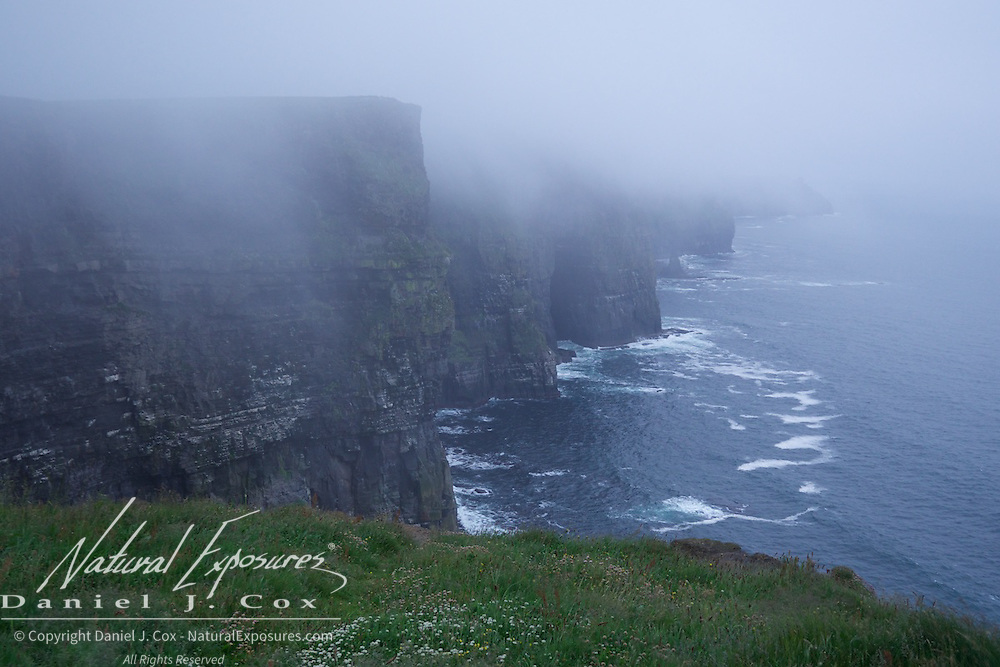 Fog rolls in to the Cliffs of Moher, Ireland.