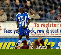 Photo: Jed Wee.<br />Wigan Athletic v Arsenal. The Barclays Premiership.<br />19/11/2005.<br />Arsenal's Cesc Fabregas is floored in the aftermath of the first Wigan goal as he appears to go down during a confrontation with Wigan scorer Henri Camara.