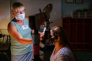 """26 JUNE 2021 - DES MOINES, IOWA: KIM GEREN, an Optometrist, checks the vision of a patient during the RAM clinic in Des Moines, Saturday, June 26. Remote Area Medical (RAM) is a nonprofit provider of free pop-up clinics. Their mission is to prevent pain and alleviate suffering by providing free, quality healthcare to those in need. They do this by delivering free dental, vision, and medical services to underserved and uninsured individuals. The clinic in Des Moines was RAM's first clinic in Iowa. RAM was hoping to see 250 people during the two day """"pop up"""" clinic.       PHOTO BY JACK KURTZ"""