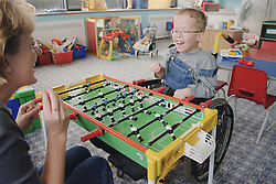 Young boy with Cerebral Palsy sitting in wheelchair playing game of table football with mother on Children's ward in hospital,
