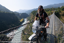 Gary Thomas riding a Royal Enfield Himalayan on the Kushma - Gyadi suspension bridge over the Modi River (the highest, at 384 feet, and longest, at 1,128 feet, suspension bridge in Nepal) in Motorcycle Sherpa's Ride to the Heavens motorcycle adventure in the Himalayas of Nepal. On the sixth day of riding, we went from Tatopani to Pokhara. Saturday, November 9, 2019. Photography ©2019 Michael Lichter.