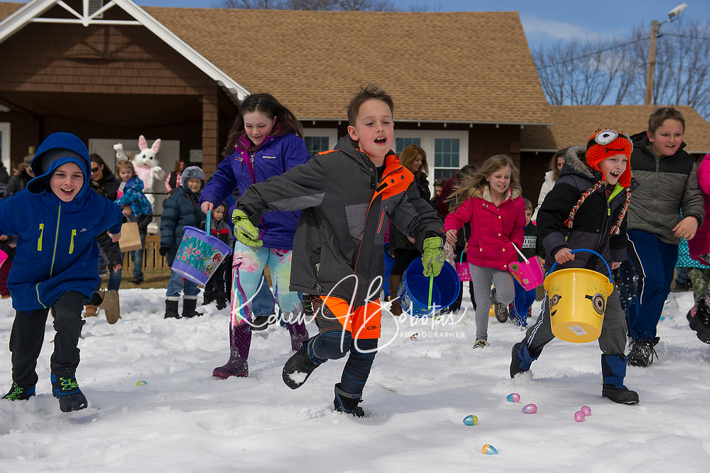 "On the sound of ""go"" children head to the field from Leavitt Park clubhouse as their search for eggs during Laconia Parks and Recreation Easter egg hunt on Sunday afternoon.  (Karen Bobotas/for the Laconia Daily Sun)"