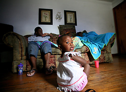 09 July 2006. New Orleans. Louisiana. <br /> Finding Faith. <br /> Faith Figueroa. A day in the life of. Faith sits on the floor as her family watch TV on a rainy day. <br /> Following a ten month search for the little girl whose face appeared on the Sept 19th, 2005 cover of Newsweek magazine, Faith's mother, Miriam Figueroa has returned to town with her three children. Faith, (1 yrs), Anfernya (5yrs) and Jacquelyn (13 yrs). <br /> Credit; Charlie Varley/varleypix.com