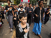 23 OCTOBER 2015 - YANGON, MYANMAR:  Men and boys beat their chests and pray during an Ashura procession in Yangon. Ashura commemorates the death of Hussein ibn Ali, the grandson of the Prophet Muhammed, in the 7th century. Hussein ibn Ali is considered by Shia Muslims to be the third imam and the rightful successor of Muhammed. He was killed at the Battle of Karbala in 610 CE on the 10th day of Muharram, the first month of the Islamic calendar. According to Myanmar government statistics, only about 4% of the population is Muslim. Many Muslims have fled Myanmar in recent years because of violence directed against Burmese Muslims by Buddhist nationalists.   PHOTO BY JACK KURTZ