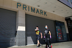 © Licensed to London News Pictures. 30/05/2020. London, UK. Members of the public wearing face coverings walk past Primark store in Wood Green, north London. Prime Minister Boris Johnson has said that from 15 June all non-essential retailers, including shops selling clothes and indoor markets can open as lockdown restrictions are eased in England after ten weeks of the coronavirus lockdown. Photo credit: Dinendra Haria/LNP