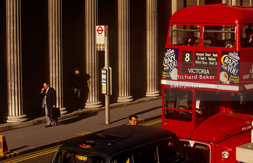 A red London double-decker Routemaster bus stops in traffic outside the pillars of the Bank of England. As a commuter waits at a bus stop opposite and passers-by come and go on Threadneedle Street, afternoon sunshine makes for a colourful urban landscape in the heart of the capital's financial district known as the Square Mile.