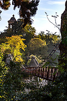 Suspension Bridge at Buttes-Chaumont Park - Parc des Buttes-Chaumont is one of the most romantic parks in Paris. It was once a quarry, so there are many rock formations and hills that are made use of in the design of the park. Jean-Charles Adolphe Alphand's plan was to re-use the rock formations to their advantage in creating a hilly terrain, with trails leading up to a pavilion on a high cliff.  There are also waterfalls and a bridge which springs from a cliff face to a pinacle crowned by a temple. Buttes-Chaumont is considered to be a triumph in landscape design