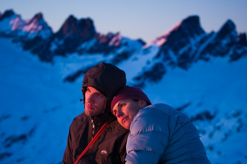 Climbers Obadiah Reid and Grace Marx watch the sunset together on a winter trip to the South Picket Range, North Cascades National Park, Washington.