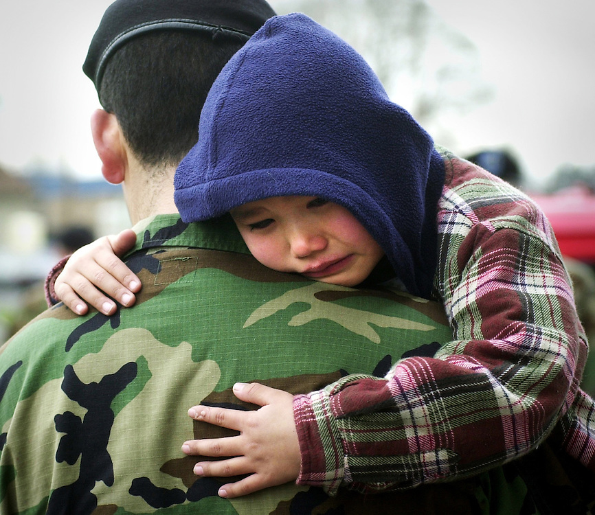 Five-year-old Michael Jennings Jr. tearfully clings to his father Michael Jennings Sr. after the deployment ceremony for the Army National Guard 162nd Infantry at the Salem Armory.