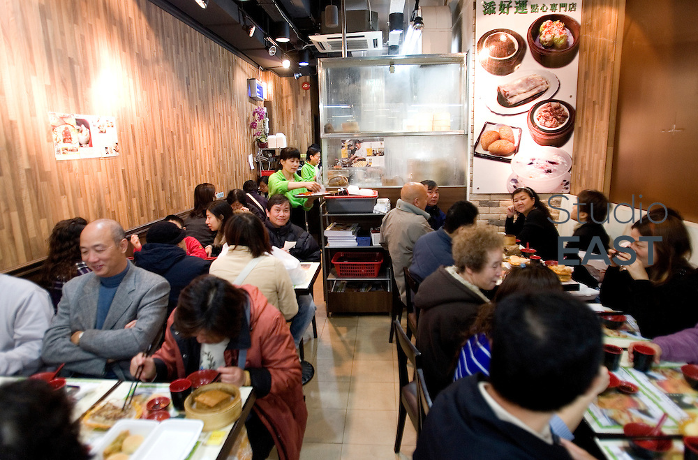 """HONG KONG, CHINA - December 18: Happy customers eat at Tim Ho Wan 32-seat restaurant on December 18, 2009 in Hong Kong, China. Tim Ho Wan restaurant is the world's cheapest Michelin star restaurant. In its 2009 Hong Kong edition, Michelin world-famous gourmet guide awarded a one-star rating to this dim sum restaurant, which serves the cheapest Michelin meals in the world. Everything on the menu is between HK$10 and HK$18 (between EUR0.89 and EUR1.60). Tim Ho Wan restaurant may be small, but it was already a big hit with the locals before the Michelin recognition. On an average day the wait to enter the 32-seat restaurant is 3 hours. Restaurant's owner Mak Kwai-pui estimates Michelin's rating only brought about 20 percent more customers, increasing his profits by only HK$1,000 a day (EUR89). And he """"sees no reason to raise prices just because they are more customers"""". (Photo by Lucas Schifres/Getty Images)"""