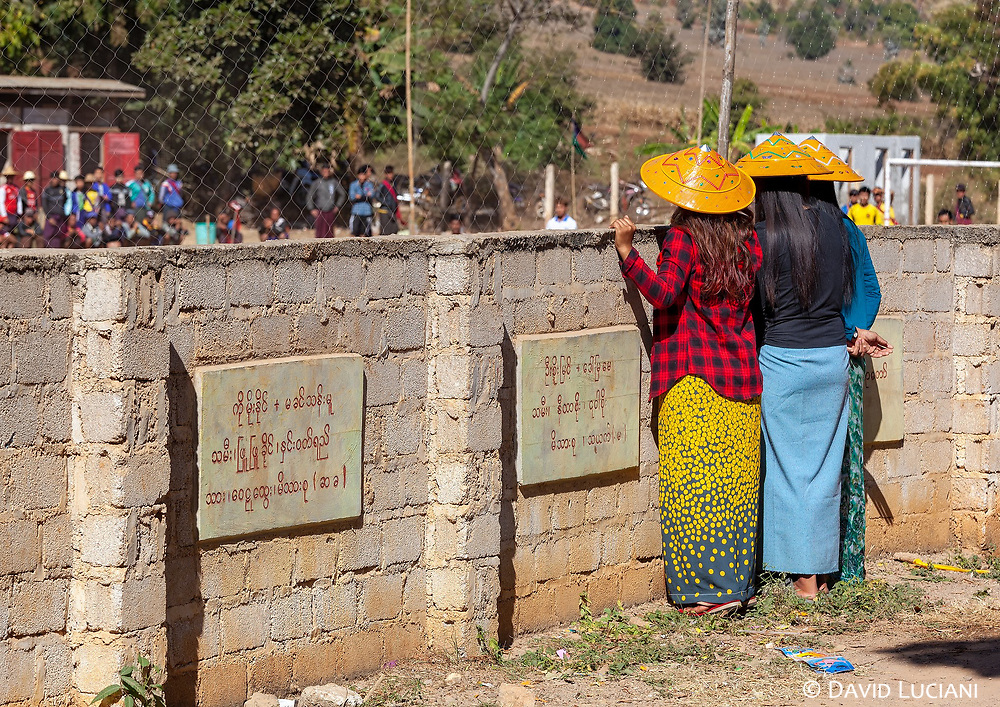 Three young ladies watching football from the other side of the wall in Sagar Village.