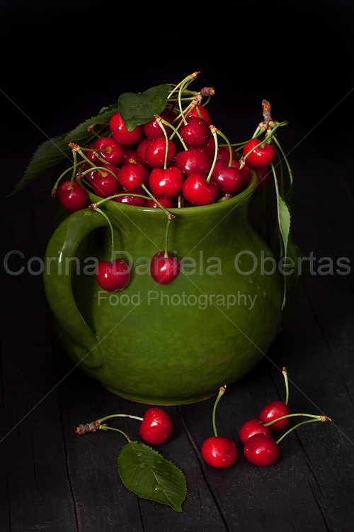 Ripe cherries in ceramic pitcher on black background.<br /> Sold exclusively through Stockfood.com