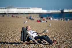 © London News Pictures. 23/09/2013 . Brighton, UK.  A conference delegate yawns as he enjoys the sunshine on Brighton beach while taking a break from the 2013 Labour Party Annual Conference which is being held at The Brighton Centre. Photo credit : Ben Cawthra/LNP