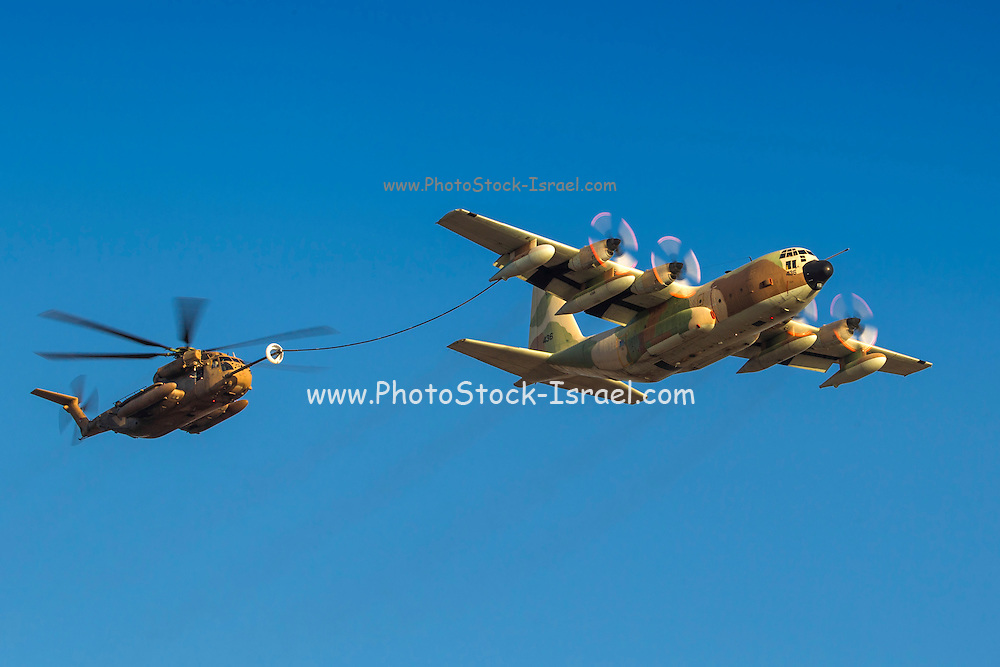 Israeli Air force (IAF) Hercules C-130 transport plane refuelling a Sikorsky CH 53 helicopters in flight.