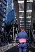 A City workers jacket lifts in the wind with modern architecture of Leadenhall where many insurance brokers and companies are grouped near Lloyds of London left in the City of London, aka The Square Mile the capitals financial district, on 3rd September 2019, in London, England.