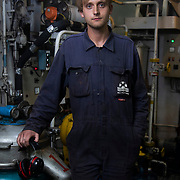 Mark, 3rd engineer. Graduate in marine engineering and currently studying physics. In the engine room below deck. Photographed at sea on patrol in the North Sea.