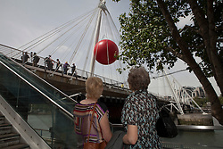 © under license to London News Pictures. 25/06/12. London, UK. New York artist Kurt Perschke's  fifteen foot inflatable Red Ball on the Golden Jubilee Bridge, South Bank. It will then move to Waterloo Bridge and Covent Garden...ALEX CHRISTOFIDES/LNP