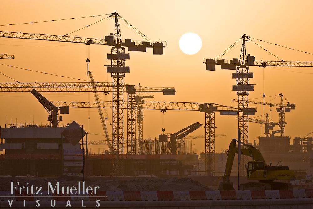 Construction cranes fill the evening sky in Dubai