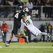 South Florida Bulls cornerback Ronnie Hoggins (19) makes an interception in front of UCF Knights wide receiver Tre'Quan Smith (4) during a NCAA football game between the University of South Florida Bulls and the UCF Knights at Spectrum Stadium on Friday, November 24, 2017 in Orlando, Florida. (Alex Menendez via AP)