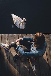 THEMENBILD - ein neugieriger Schwan neben einem Steg wo eine Frau mit einem Fotoapparat sitzt während der Corona Pandemie, aufgenommen am 17. April 2019 in Hallstatt, Österreich // a curious swan next to a jetty where a woman is sitting with a camera during the Corona Pandemic in Hallstatt, Austria on 2020/04/17. EXPA Pictures © 2020, PhotoCredit: EXPA/ JFK