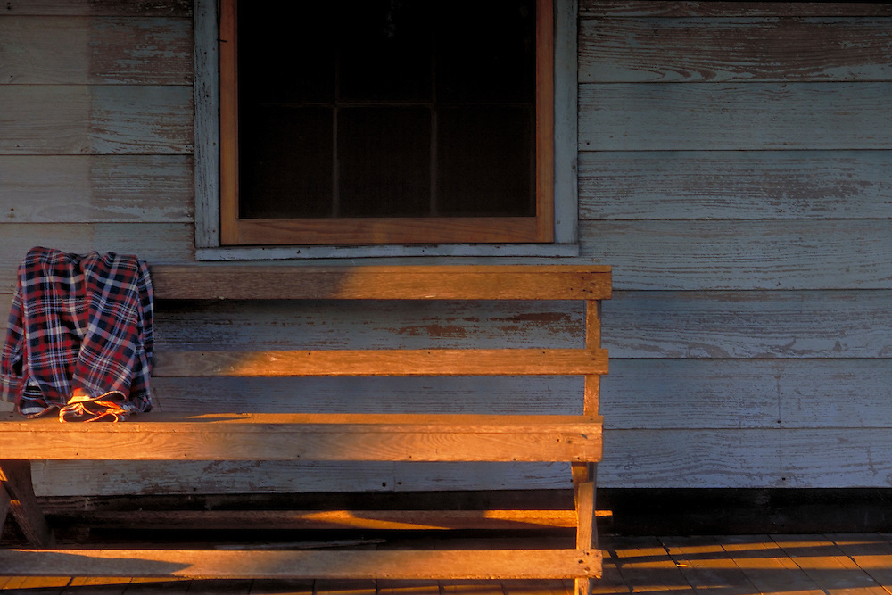 Sunset in the small Texas town of Wimberley where sunlight streams across the porch and wooden bench that has a well worn flannel shirt draped over it. The house has thin white washed paint on the wooden horizontal slats. A screened window is behind the bench.Almost The structure is a 200 year old dog-trot log cabin.