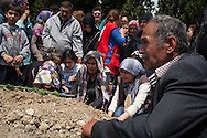 Family members cry at one of the many graves at the cemetery in Soma, where miners are being buried. An electrical fault caused an explosion in the shaft resulting in at least 282 workers being killed in the disaster. Soma, Western Turkey.