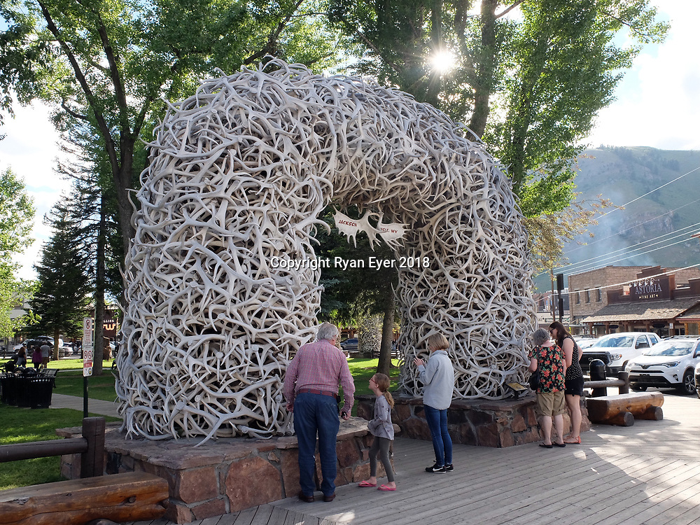 """JACKSON, Wyoming - 21 June 2018 - Tourists look at one of the four arches made of the antlers of Elk in the town of Jackson in Wyomig. The Elk Antler Arches are is made up of around 2,000 antlers. No elk were harmed in the making of the arches. Elk naturally shed their antlers each year and they are collected from the ground. The antlers are then weaved around a steel frame one at a time. There are four elk antler arches guarding the corners of Jackson's George Washington Memorial Park, more commonly called the Town Square. The town, often mistakenly called Jackson Hole, derives its name from """"Jackson Hole"""", the valley in which it is located. Picture: Ryan Eyer"""
