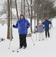 Amanda Brunt followed by Debbie and Steve Birch enjoy the gently falling snow as they head out onto the cross country trails at Bolduc Park Saturday morning for week two of skiing lessons offered by the Gilford Parks and Recreation department. (Karen Bobotas/for the Laconia Daily Sun)