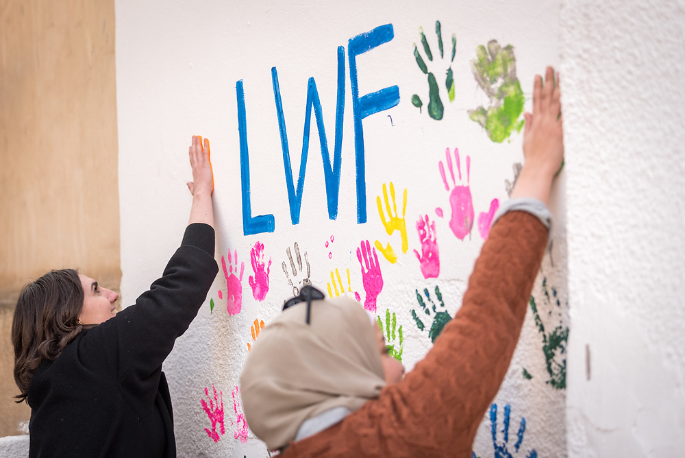 17 February 2020, Zarqa, Jordan: Lutheran World Federation staff and visitors paint their handmarks on a wall at the LWF community centre in Zarqa. Through a variety of activities, the Lutheran World Federation community centre in Zarqa serves to offer psychosocial support and strengthen social cohesion between Syrian, Iraqi and other refugees in Jordan and their host communities.