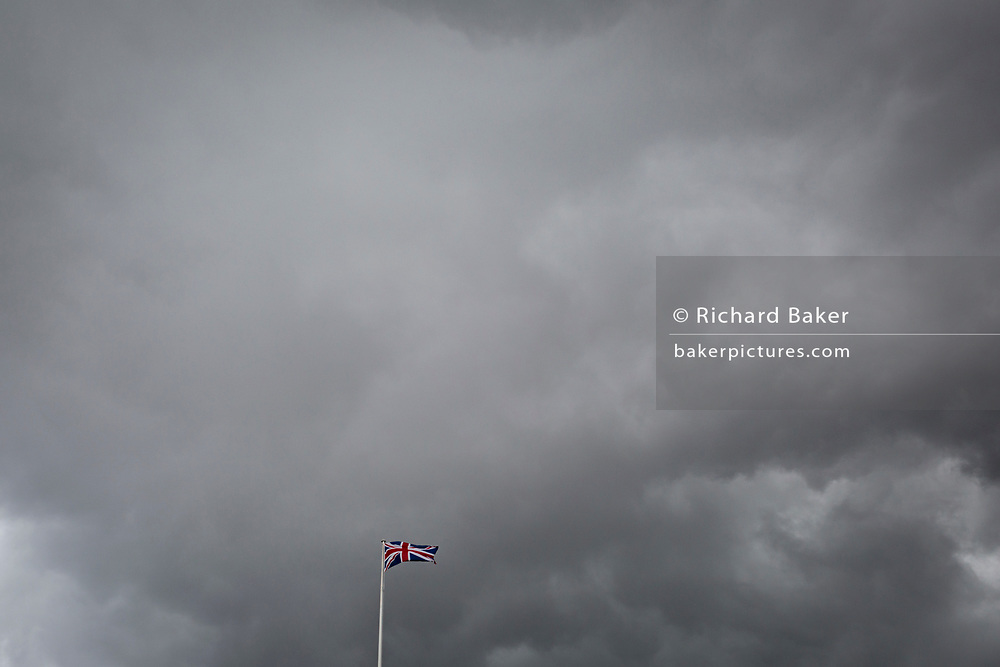 As an approaching storm nears, the British Union Jack flag flies in darkening skies - a metaphor for Brexit, on 1st October 2019, in London, England.