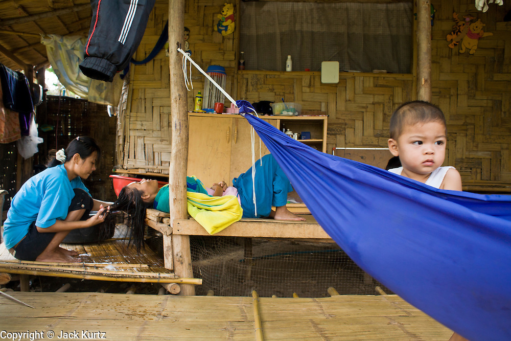 18 FEBRUARY 2008 -- BONG TI, KANCHANABURI, THAILAND: Burmese women wash their hair while a child waits in a hammock at the Bamboo School in Bong Ti, Thailand, about 40 miles from the provincial capital of Kanchanaburi. Sixty three children, most members of the Karen hilltribe, a persecuted ethnic minority in Burma, live at the school under the care of Catherine Riley-Bryan, whom the locals call MomoCat (Momo is the Karen hilltribe word for mother). She provides housing, food and medical care for the kids and helps them get enrolled in nearby Thai public schools. Her compound is about a half mile from the Thai-Burma border. She also helps nearby Karen refugee villages by digging water wells for them and providing medical care.  Photo by Jack Kurtz