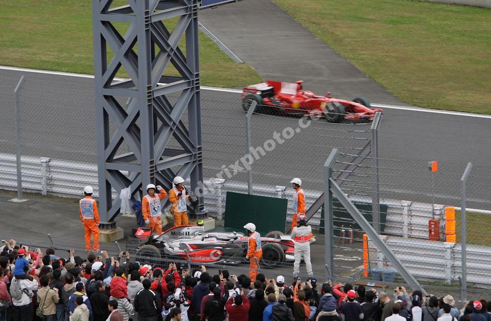 Heikki Kovalainen (McLaren-Mercedes) retires from the 2008 Japanese Grand Prix at Fuji Speedway with Kimi Raikkonen (Ferrari) passing. Photo: Grand Prix Photo