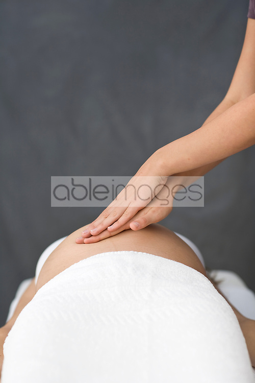 Close up of female massage therapist's hands massaging pregnant woman stomach
