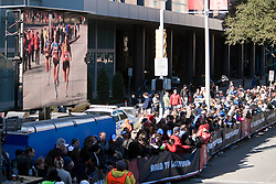 jumbotron TV showing race in progress at finish line area, leaders Flanagan, Davila and Goucher
