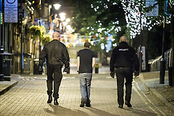 "© Licensed to London News Pictures . 10/08/2011 . Manchester , UK . Jeremy Joseph (c) walks along Canal Street in Manchester's "" Gay Village "" , flanked by security guards , as disorder spreads to Manchester during a 4th night of rioting and looting , following a protest against the police shooting of Mark Duggan in Tottenham . Photo credit : Joel Goodman/LNP"