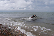 A sea swimmer dives into the cold tidal waters of the Thames Estuary, on 25th July 2021, in Whitstable, England.