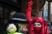 A member of the Extinction Rebellion Red Rebel Brigade raises a clenched fist in front of a Metropolitan Police officer during the first day of Impossible Rebellion protests in the Covent Garden area on 23rd August 2021 in London, United Kingdom. Extinction Rebellion are calling on the UK government to cease all new fossil fuel investment with immediate effect.