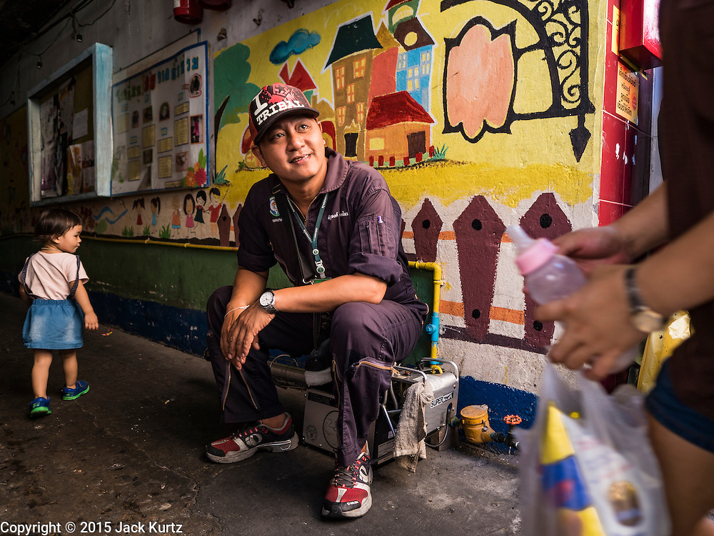 02 DECEMBER 2015 - BANGKOK, THAILAND: A mosquito control worker waits to start spraying in a neighborhood in Bangkok. The Public Health Ministry in Thailand said that more than 111,000 cases of dengue fever have been reported in 2015, an increase of more than 200% over the number of cases of dengue fever reported 2014. Dengue fever is a virus spread by mosquito and is endemic in southeast Asia. Thai health officials are aggressively spraying areas where mosquitoes are known to live and leading public information and education sessions on preventing dengue fever. There is no vaccine for dengue fever, so preventing dengue means avoiding mosquitoes.        PHOTO BY JACK KURTZ