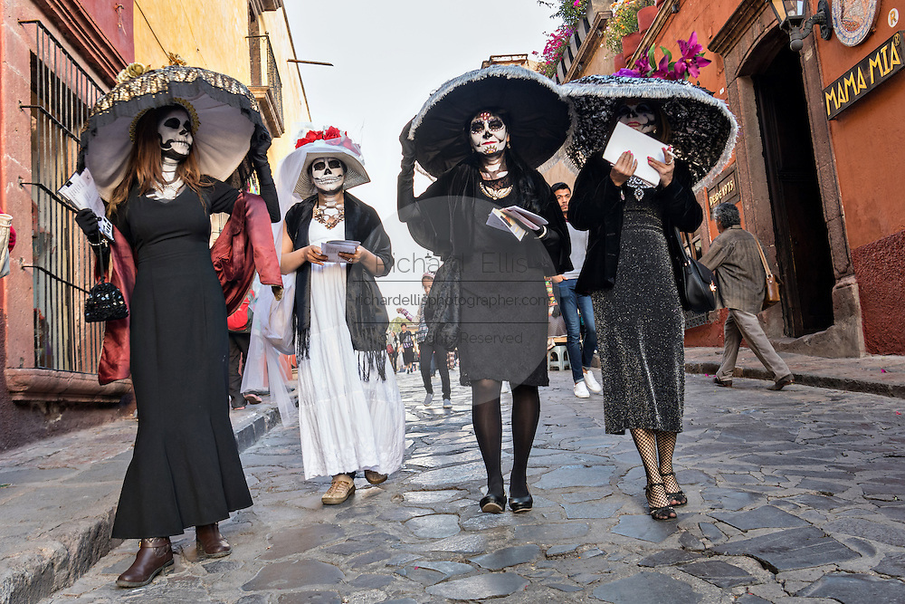 Women dressed as La Calavera Catrina parade through the streets during the Day of the Dead festival October 28, 2016 in San Miguel de Allende, Guanajuato, Mexico. The week-long celebration is a time when Mexicans welcome the dead back to earth for a visit and celebrate life.